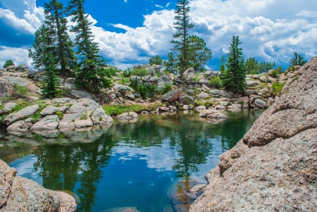 Puffy white clouds, mountain boulders and fir trees reflected mountain lake on a sunny day   photo
