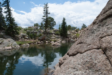 Puffy white clouds on a sunny day with mountain boulders and rocks surrounding a mountain lake  photo