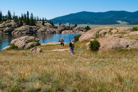 paddler: backpackers in a meadow by mountain lake under blue sky with Rockies in background Stock Photo