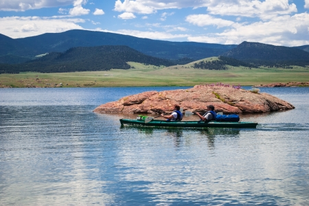 roughing: Kayakers on mountain lake with the Rocky Mountains in the background on a sunny day