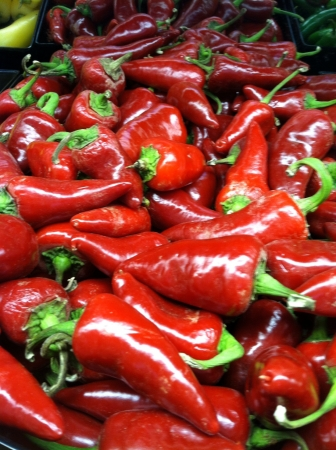 Loose bunch of fresh red organic cayenne peppers at market