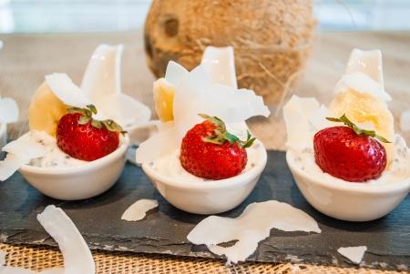 Gluten free greek yogurt, chia seeds, sliced strawberries, bananas and organic coconut chips in small spoons photo