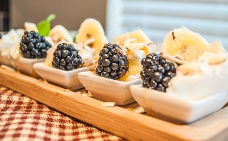 Gluten free small spoons of greek yogurt, organic blackberries, sliced bananas, almonds and honey