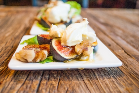 Gluten free small plate of fresh mission figs, walnuts, cheeses and honey Stock Photo