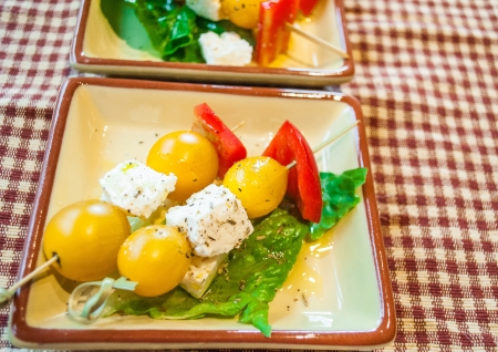 Small plates of yellow organic tomatoes, feta cheese, red peppers threaded onto bamboo skewers served as gluten free appetizer