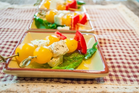 free dish: Close up of gluten free dish of yellow organic tomatoes, red peppers, feta cheese as a small bite appetizer  Stock Photo