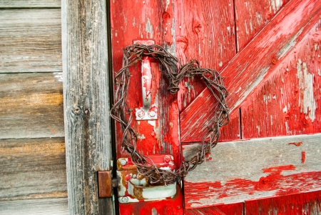 barbed wire heart hanging on old red barnwood door in sunlight photo