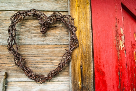Barbed wire heart hanging on old wood in the sunlight with a red door on the right photo