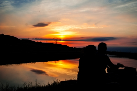 reflect: Sunsetting  on water with a silhouette of couple riding four wheeler reflect