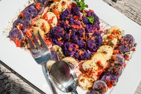 Cold gluten free vegetable salad with a viniagrette being served on a wooden patio table Stock Photo