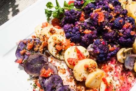 Gluten free purple and white potatoes, purple cauliflower on a patio table with viniagrette of tomatoes, bacon