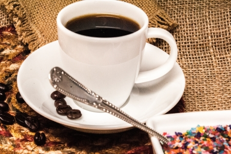 forground: White cup of coffee against a background of burlap with colored sugar and spoon in the forground Stock Photo