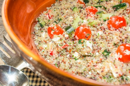 Mediterranean quinoa salad with tomatoes and feta cheese close up photo