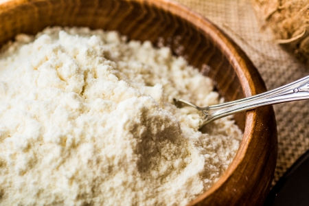 Close up of organic coconut flour in wooden bowl Stock Photo