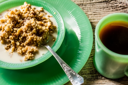 glycemic: Healthy hot millet porridge in a jadeite bowl with a cup of coffee