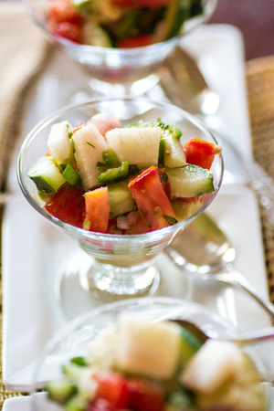 Cold cucumber tomato avocado jicama salsa in mini glass dishes photo