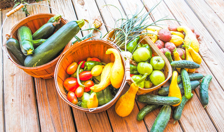 baskets of farm fresh organic vegetables on wooden table  photo
