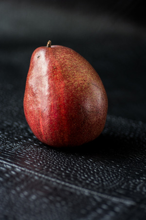 Red pear under natural light against black background