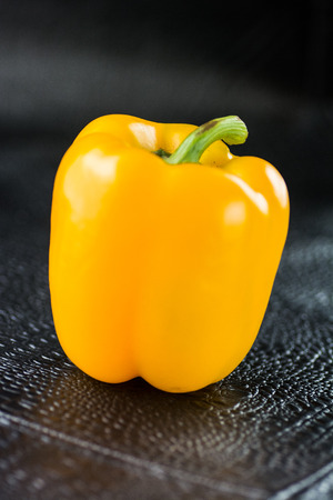 Contrasted yellow bell pepper close up on black background