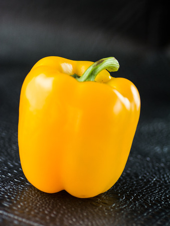 Yellow bell pepper close up on black background