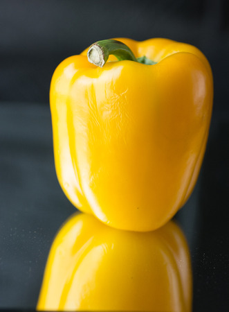 Yellow bell pepper close-up reflected on mirror with black background