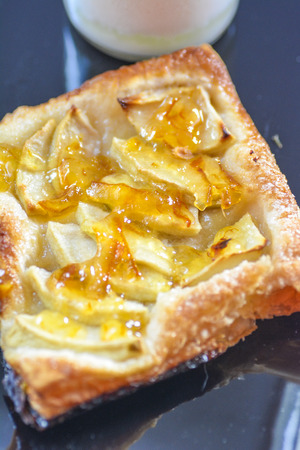 Individual French apple tart on black plate