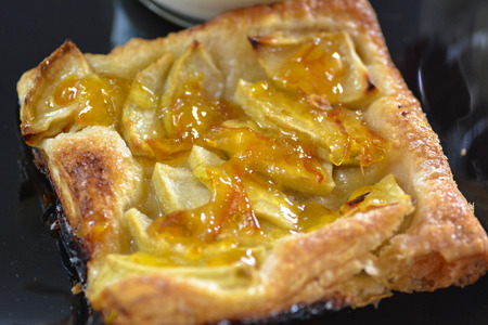 French apple tart close up on black plate Stock Photo