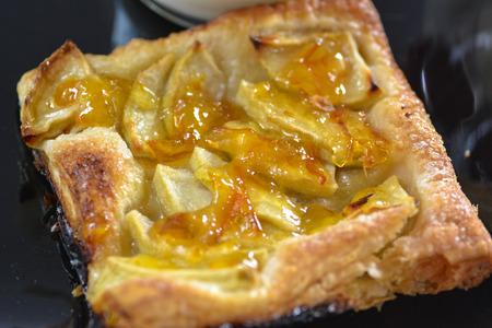 French apple tart close up on black plate Reklamní fotografie