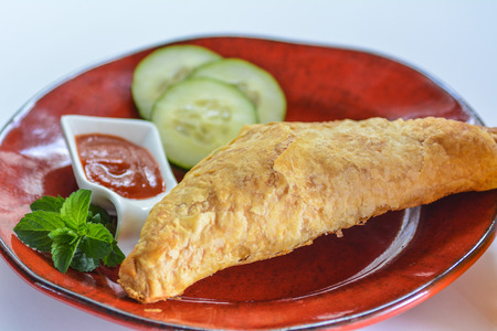 Breakfast empanada on a red plate with sirracha and cucumber