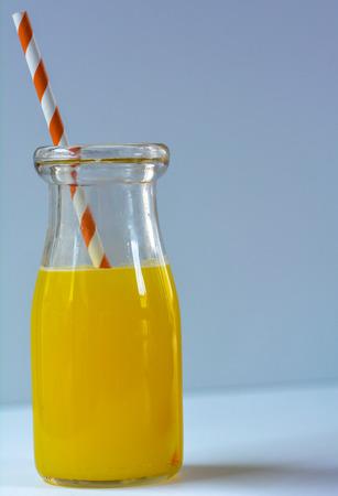 orange juice in a vintage milk bottle with a paper straw