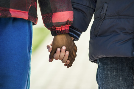 held: 2 boys of different nationalities are held by the hand Stock Photo