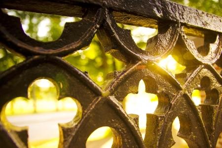 Christelijke architectuur, oude antieke hek van de kerk met kruis bezuinigingen en fel licht van achter