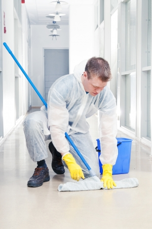 Man cleaning office wearing protective overalls photo