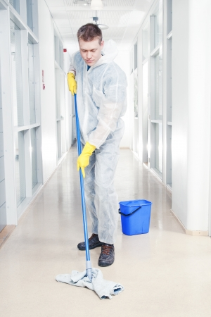 mop floor: Man cleaning office wearing protective overalls