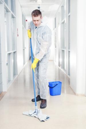 Man schoonmaak kantoor dragen beschermende overalls Stockfoto