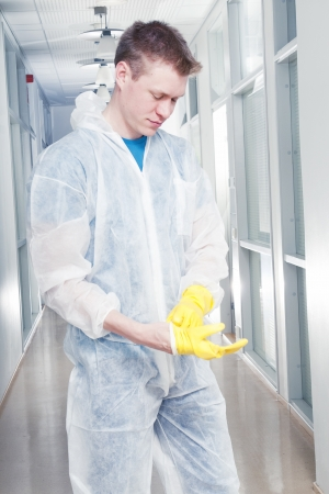 Cleaner man in protective overalls putting rubber gloves on photo