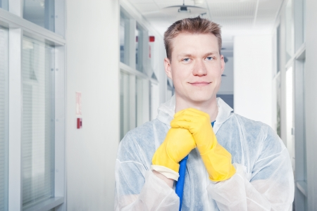 Smiling cleaner man wearing protective overall
