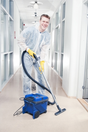 cleaning an office: Man cleaning office with vacuum wearing protective overalls
