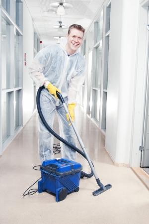 Man schoonmaak kantoor met vacuüm dragen van beschermende overalls