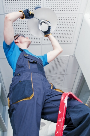 Janitor repareren kapotte lamp in de gang