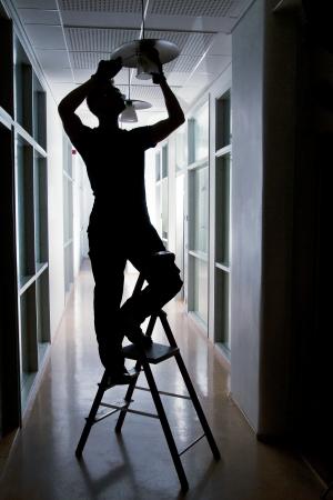 Silhouette of a janitor repairing broken lamp in corridor