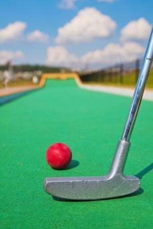 teen golf: Primer plano de bate y pelota de golf en miniatura en el inicio de la pista Foto de archivo