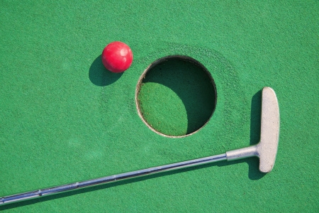 playing golf: Close-up of miniature golf hole with bat and ball