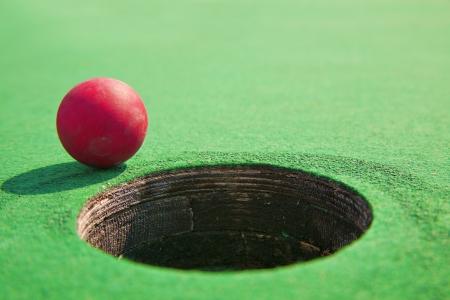 teen golf: Primer plano de la mini-pelota de golf al lado del agujero Foto de archivo