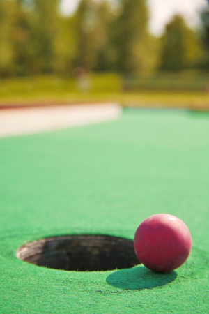 Close-up of mini golf ball next to hole