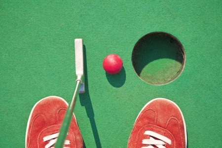 Close-up of miniature golf hole with bat and ball photo