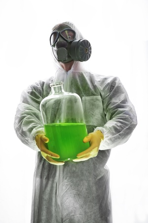 Man with gas mask and protective suit carrying hazardous chemical waste photo