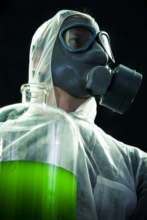 hazardous waste: Man with gas mask and protective suit carrying hazardous chemical waste