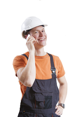 Construction worker talking to mobile phone, isolated on white photo