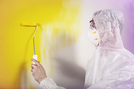 Painting wall yellow wearing protective clothes with colorful roller photo